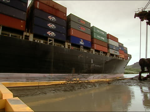 PAN, MS three men looking at cargo ship loaded with containers leaving dock, Panama Canal