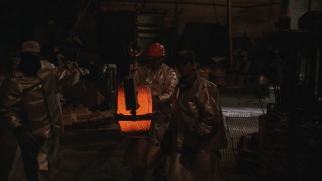 MS, Three men moving hot liquid copper in cable and wire factory
