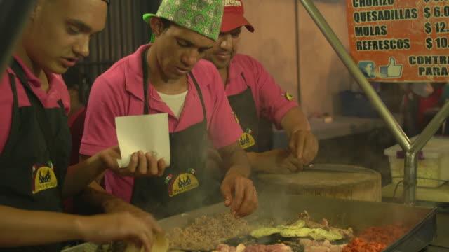 Three men prepare tacos at outdoor taco stand