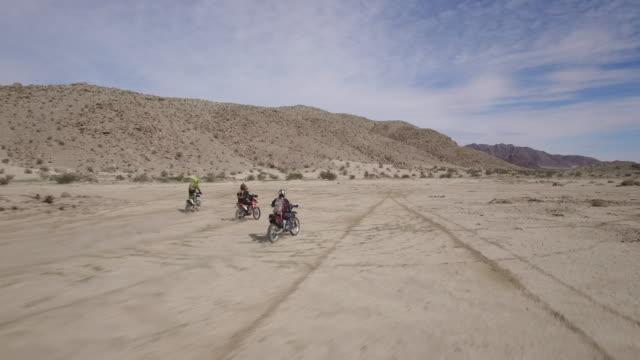 Three men riding dirtbikes