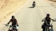 Three men riding motorcycles along road
