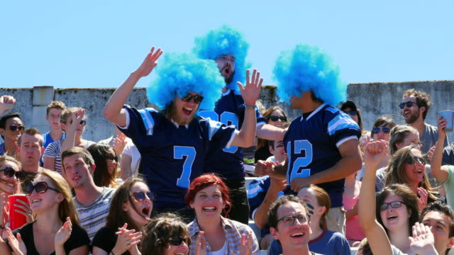 MS Three men wearing football team jerseys and wigs celebrating with other fans in stadium after team scores touchdown