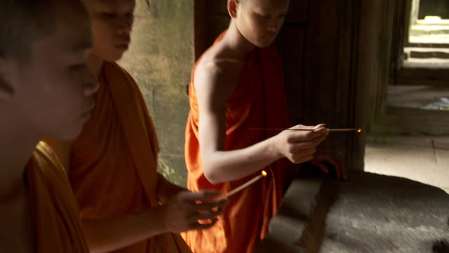 MS Three monks dressed in orange robes lighting incense sticks in Bayon Temple at Angkor Thom / Siem Reap, Siem Reap Province, Cambodia