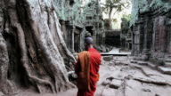 MS Three Monks in Saffron robes walking  inside of temple  / Cambodia