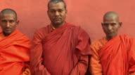 SLO MO MS PAN Three monks standing against wall / Bodh Gaya, Bihar, India