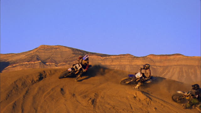 SM HA WS Three motocross riders driving on dirt hill in desert / Colorado, USA