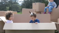 three multicultural babies sitting in cardboard boxes