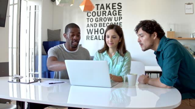 Three multi-ethnic friends doing homework together