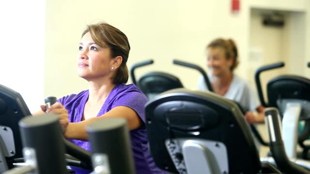 Three multi-ethnic women exercising in gym