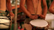 PAN Three musicians playing small drums on a beach for a party