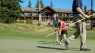 Three people playing golf