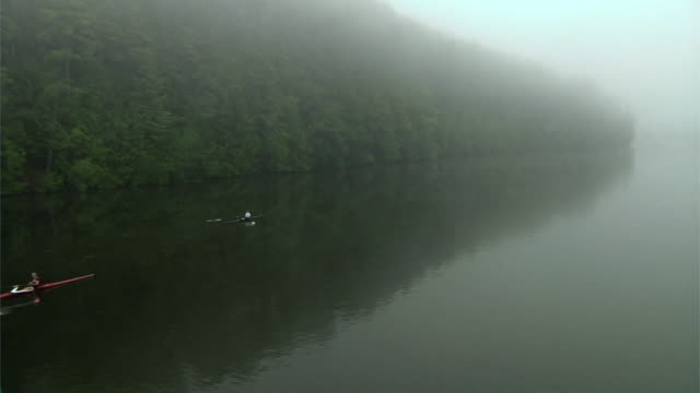 HA WS Three people rowing past in single sculls on the Connecticut River at dawn/ Hanover, New Hampshire, USA