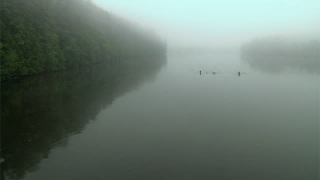 HA WS Three people rowing past in single sculls on the Connecticut River at dawn / Hanover, New Hamshire, USA