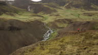 Three people walk to edge of cliff overlooking stream in Iceland