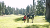 Three people walking on a golf course with sporting equipment