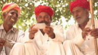 Three rajasthani senior men watching mobile phone, Jaisalmer, Rajasthan, India