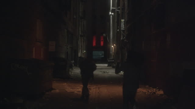 RECREATION Three runners fleeing down a dark alley / California, United States