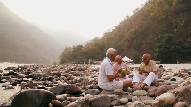 Three senior men drinking coconut water at riverbank, Ganges River, Rishikesh, Uttarakhand, India