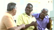Three senior men sitting on bench, talking, laughing