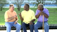 Three senior men sitting on bench, talking