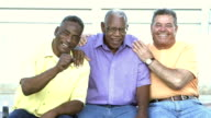 Three senior men sitting outdoors, looking at camera