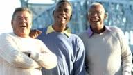 Three senior men talking, laughing outdoors