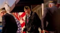 Three senior war veterans walking on sidewalk with American flags hanging in background / California