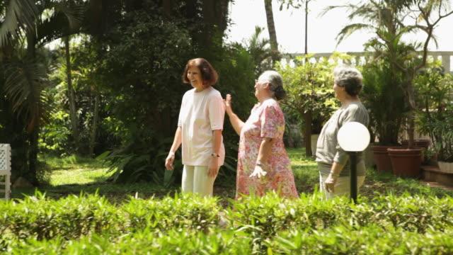 Three senior women walking in a garden