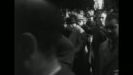 Three shots of funeral cortege marching along street crowds on either side / hearse passing by camera people in procession behind it walking past...