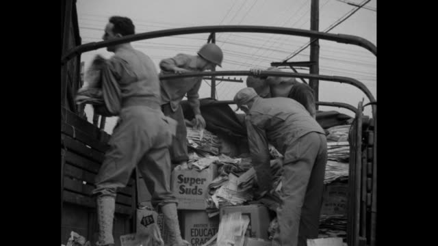 Three shots of men unloading bundles of paper from truck onto freight car / Boy Scouts giving bundles of paper to Boy Scouts at counter of small shed...