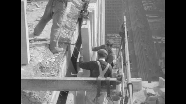 Three shots of two men putting in part of concrete wall on roof of building / four shots of two men standing on platform and man above them putting...