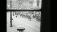 Three POV shots through window from inside building of French soldiers and French cavalry moving through crowd of people on sidewalk / Note exact...