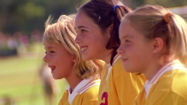 MS PROFILE three smiling girls in soccer uniforms in line / blonde girl on end gives thumbs up
