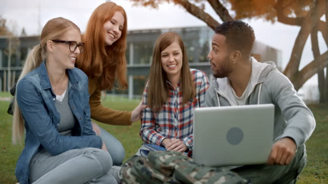 Three students greeting their female Caucasian friend joining them in the park