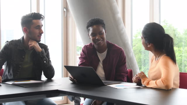 Three students using laptop and discussing in college