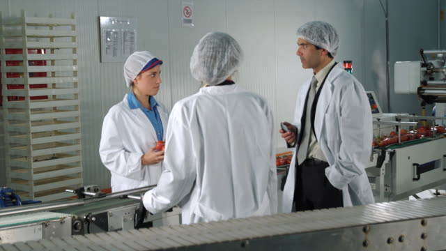MS DS Three technicians in protective clothing conferring in food processing plant / Algarrobo, Malaga, Spain
