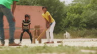 Three teenage boys playing cricket, Haryana, India