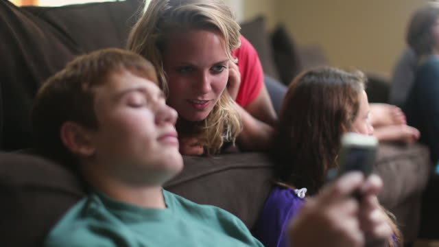 CU SELECTIVE FOCUS Three teenagers (14-15, 16-17) hanging out in living room, looking at mobile phone / Cazenovia, New York, USA