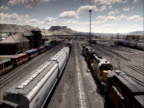 Three trains haul freight through a busy railroad yard.