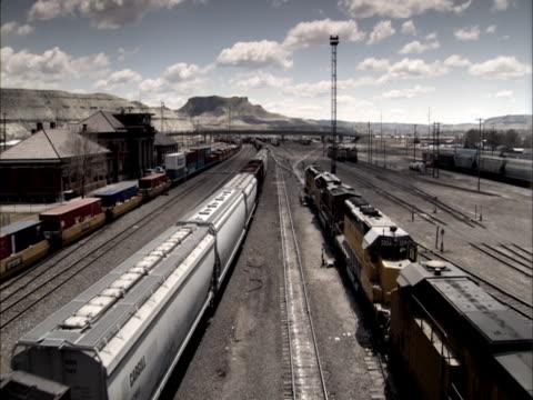 Three trains haul freight through a busy railroad yard.