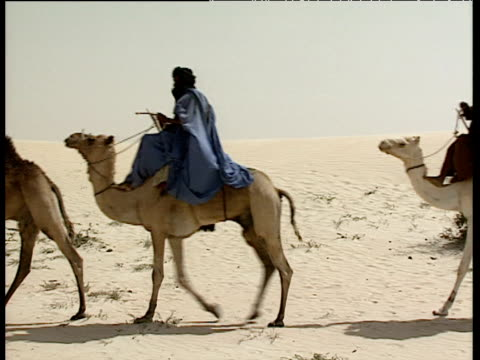 Three Tuareg tribesmen in traditional turbans and robes ride camels across white sands of desert