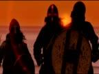 Three viking men run towards camera holding up shields and swords under orange sky