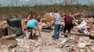 WS three women clear debris and rubble Deadly tornadoes ripped through the region starting on April 27 leaving more than two dozen dead The storm...