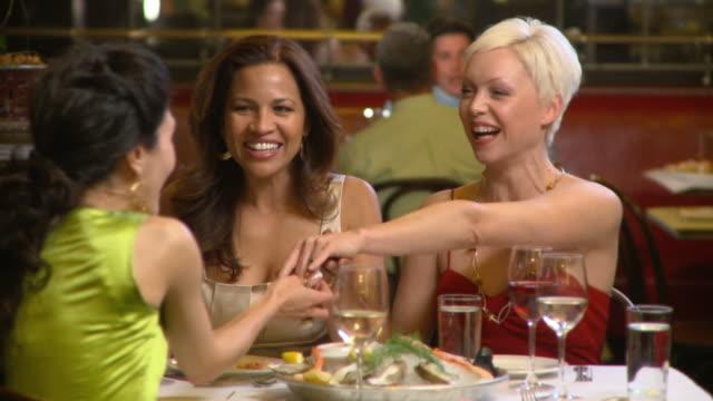 MS Three women dining at upscale restaurant, celebrating engagement, admiring ring, Richmond, Virginia, USA