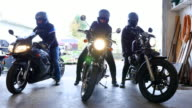 Three women on motorcycles backing out of garage to go on ride