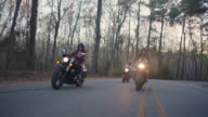SLO MO. Three women on motorcycles drive in formation down long curvy forest highway.