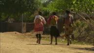 Three women walk along a dirt road in a village in Malawi.