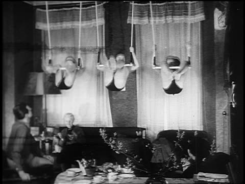 B/W 1955 three young boys hanging from one arm + one leg on trapeze in house as couple watches