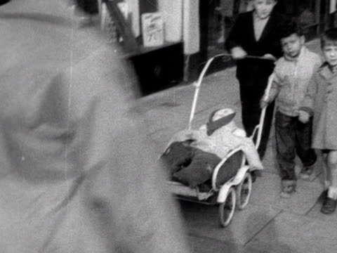 Three young children push a pram down a street carrying a home made guy for bonfire night 1962