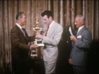 1954 three young men receiving trophies from two older men in award ceremony / USA